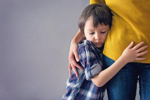 Niño abrazado a su madre con miedo porque sufre el síndrome de la cabaña.