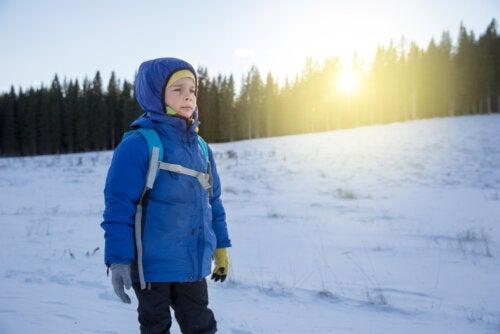 Niño en la nieve superando el frío y las adversidades gracias a las claves para criar hijos resilientes.