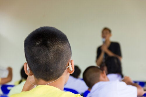Niño sordo con audífonos en clase.