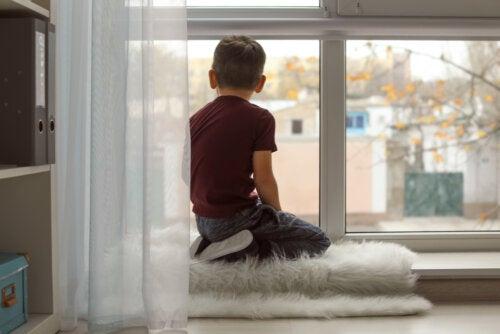 Niño TEA mirando por la ventana.