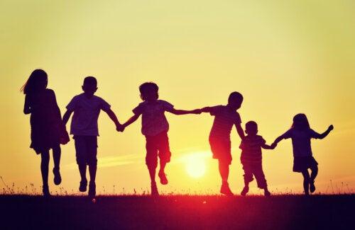 Niños agarrados de la mano durante una puesta de sol.
