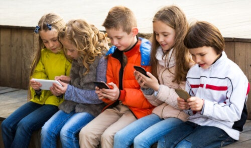 Niños mirando sus redes sociales en el móvil.
