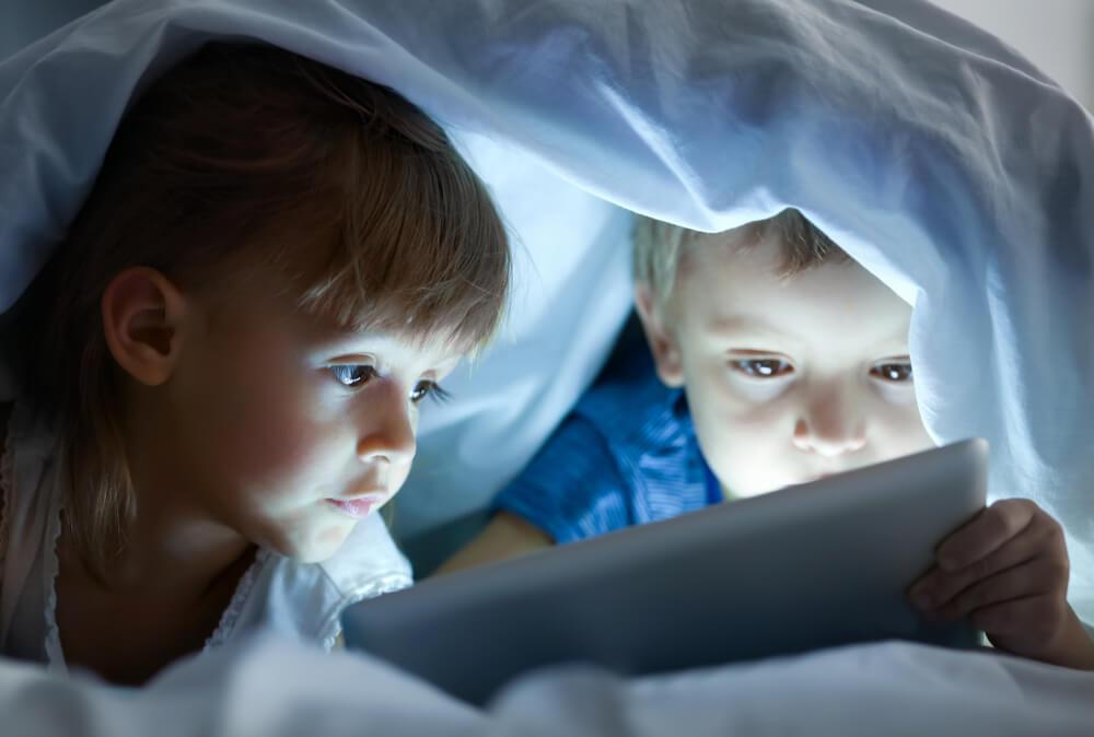Des enfants regardent un film sous les couvertures sur une tablette.