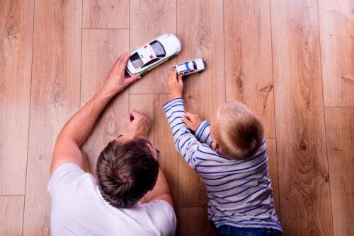 Padre e hijo jugando a los coches juntos.