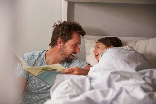 Padre leyendo uno de los libros de la Colección Iguales a su hija en la cama antes de dormir.