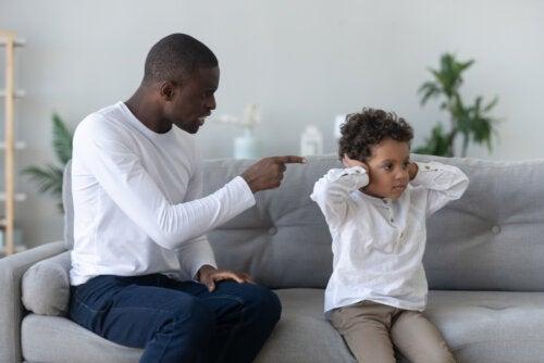 Padre regañando a su hijo intentando evitar gritar a su hijo.