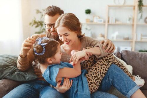 Padres haciéndole cosquillas a su hija en el sofá.
