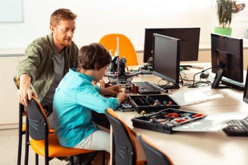 Profesor con su alumno promoviendo una educación STEM en clase de tecnología.