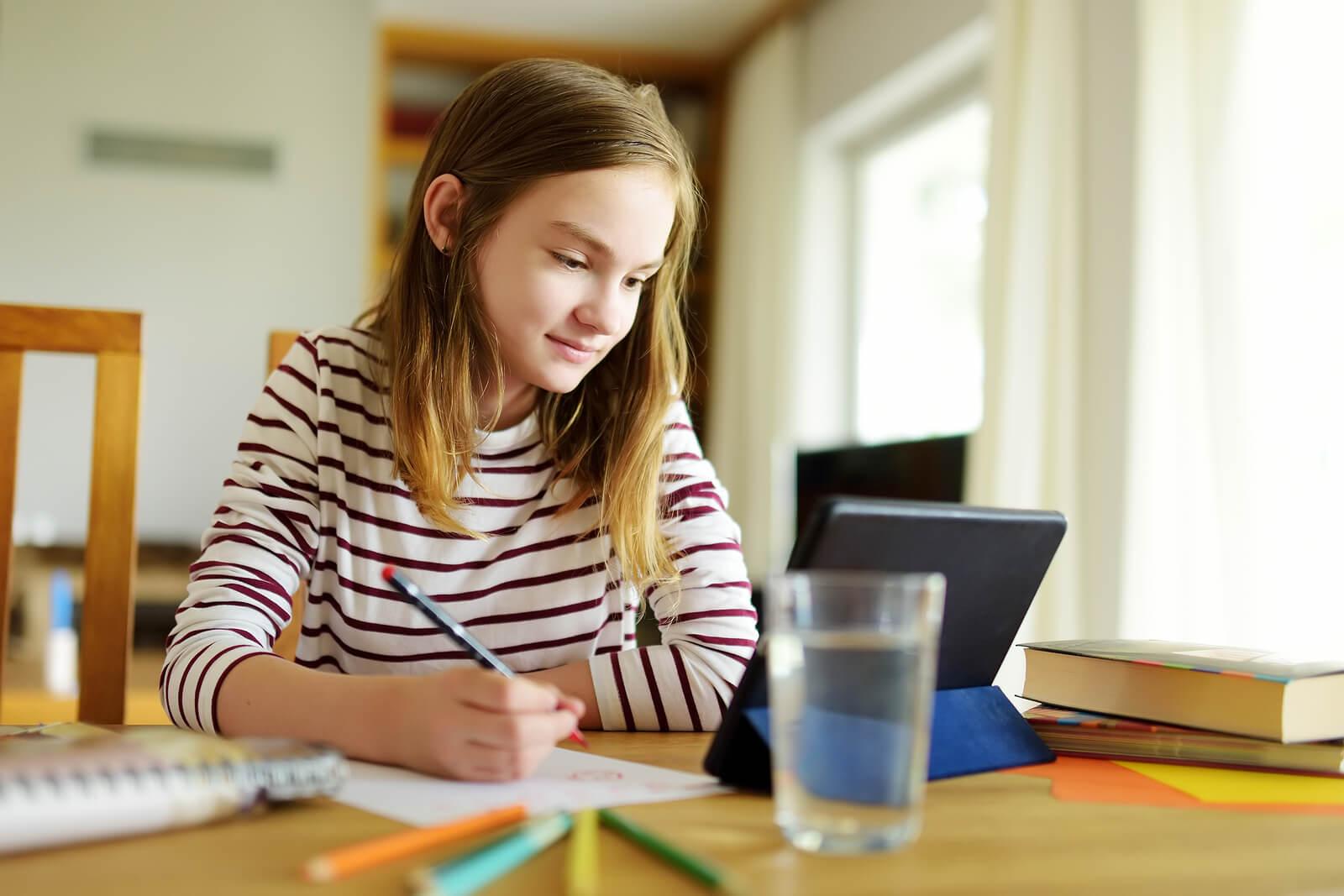 Adolescente estudiando en su habitación tras organizarse la sesión de estudio.