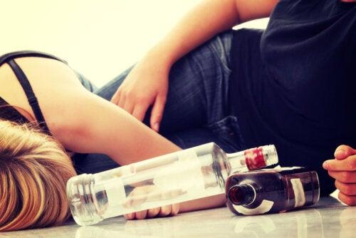 Adolescentes tumbados en el suelo borrachos después de beber alcohol.