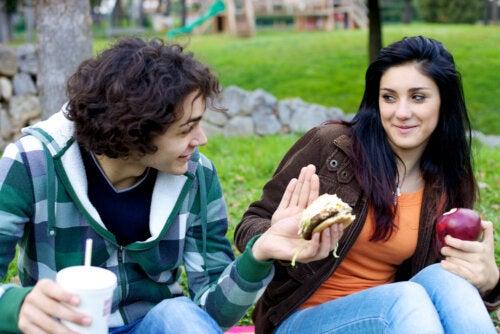 Chica rechazando una hamburguesa y comiendo una manzana debido a que padece ortorexia.