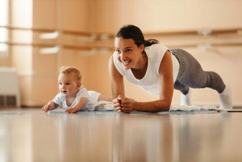Bebé imitando a su madre mientras hace ejercicio.