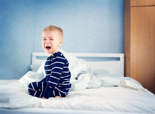 Bebé llorando porque no quiere dormir debido a la regresión del sueño.