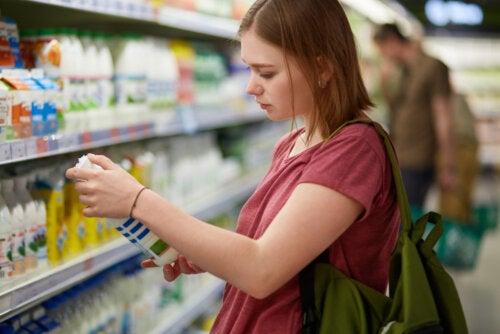 Chica adolescente analizando las etiquetas de los alimentos que compra debido a que padece ortorexia, es decir, obsesión por la comida sana.