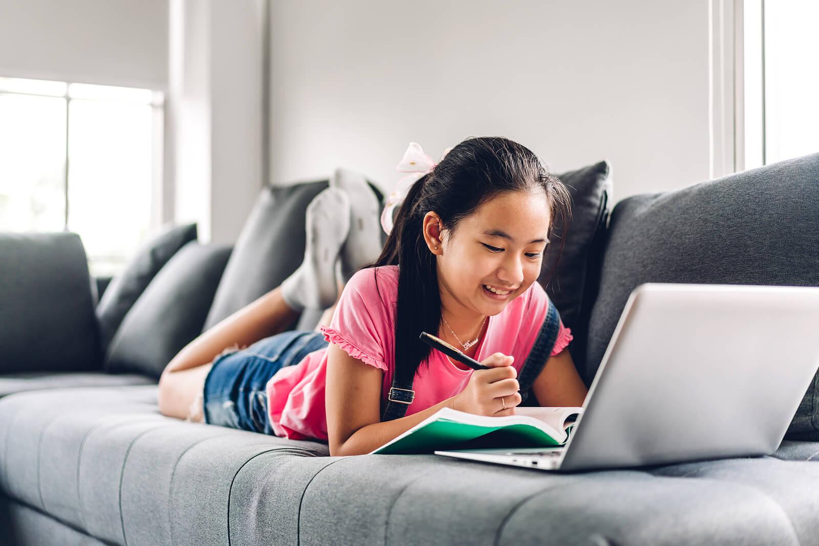 Chica estudiando en el sofá aplicando las técnicas de autorregulación del aprendizaje.