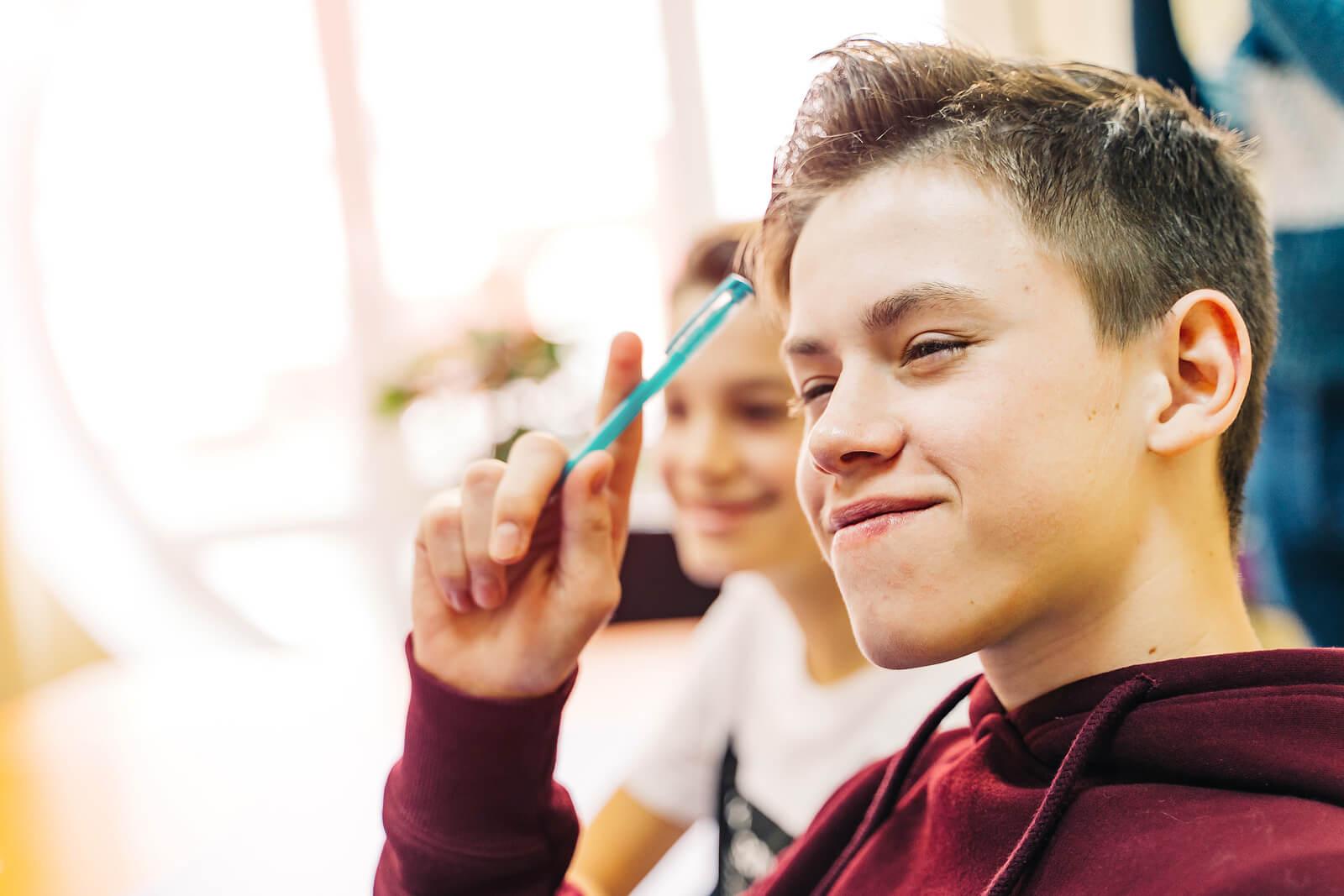 Chico adolescente aprendiendo a tomar buenos apuntes en clase.