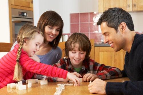 Familia jugando a juegos de mesa, una de las prácticas que refuerzan la relación entre padres e hijos.