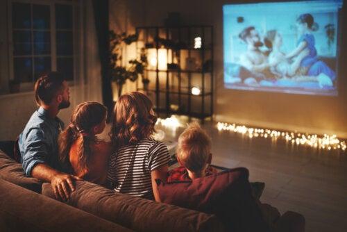 Familia viendo una película en casa a modo de cine.