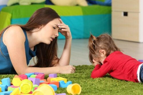 Madre frustrada intentando seguir los consejos para no consentir demasiado a los niños.