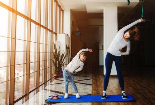 Madre e hija haciendo ejercicio en casa para sobrellevar la cuarentena.