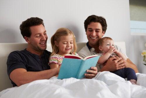 Padres leyendo un cuento a sus hijos en la cama mientras llevan a cabo la actividad 12 mese, 12 personajes para fomentar la lectura en los niños.