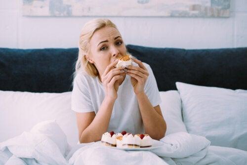 Mujer comiendo pasteles en la cama porque tiene ansiedad por la comida.