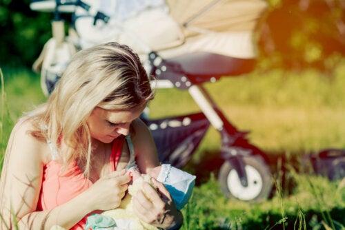 Mujer dando el pecho a su bebé en el parque.