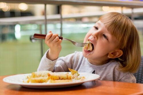 Niña comiendo en un restaurante el menú infantil.