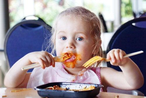 Niña comiendo pasta con tomate en un restaurante.