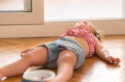 Niña en plena adolescencia infantil tumbada en el suelo enfadada.