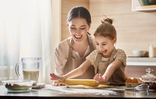 Madre con su niña ayudando en la cocina para ser una mamá divertida.