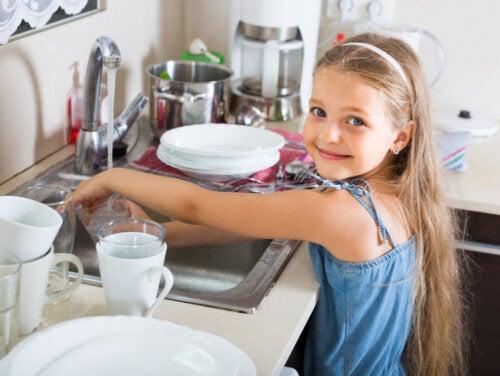 Niña con una gran independencia infantil fregando sus platos después de comer.