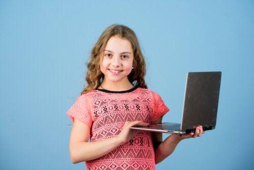 Niña con el ordenador en las manos preparada para sus clases en la escuela de inglés online.