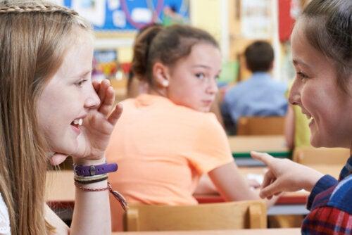 Niñas riéndose de una compañera en clase y dando el perfil del niño acosador.