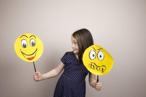 Niña con unas caras amarillas dibujadas representando emociones.