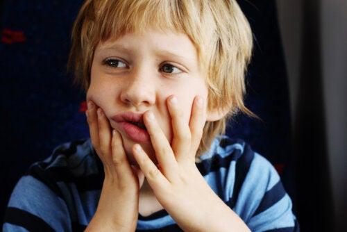 Niño con autismo pensando en los libros adaptados.