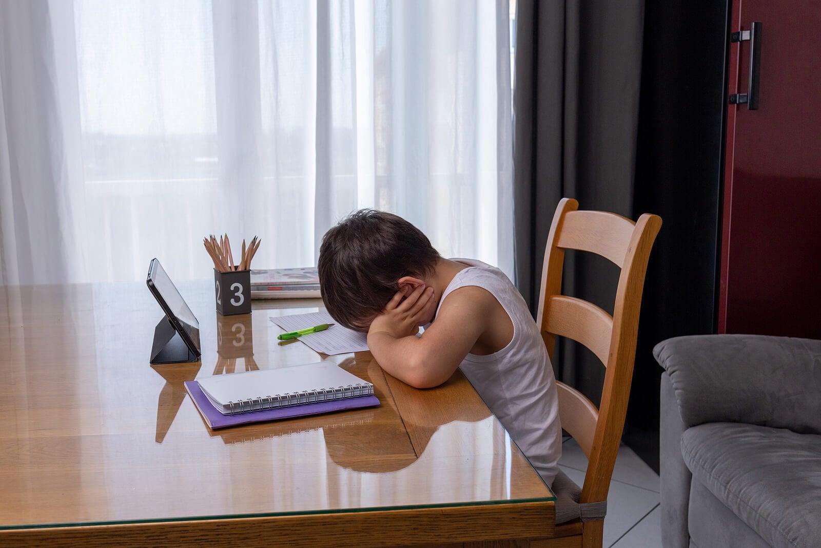 Niño cansando en el momento de hacer los deberes.