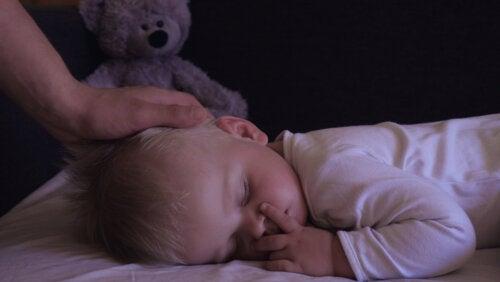 Madre acariciando la cabeza de su hijo mientras utiliza la técnica de la hipnopedia mientras duerme.