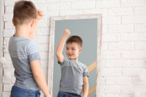 Niño contento con su imagen corporal frente al espejo.