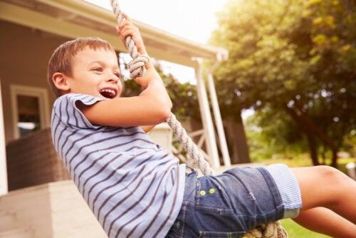 Niño feliz jugando al aire libre trabajando el merecimiento.