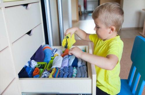 Niño independientes guardando su ropa en el armario.