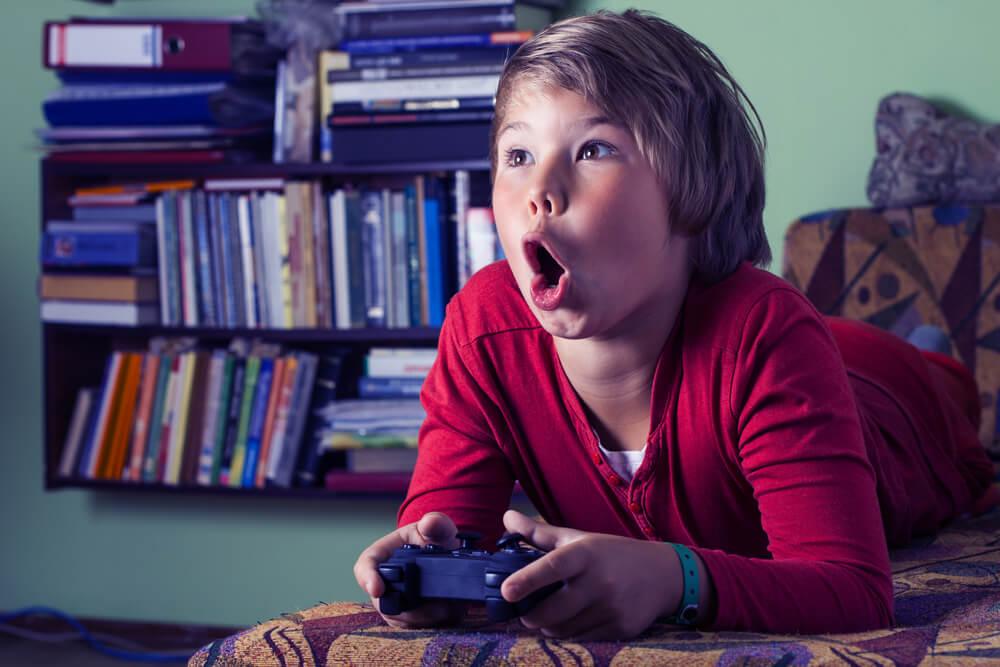 Niño jugando a videojuegos entusiasmado.