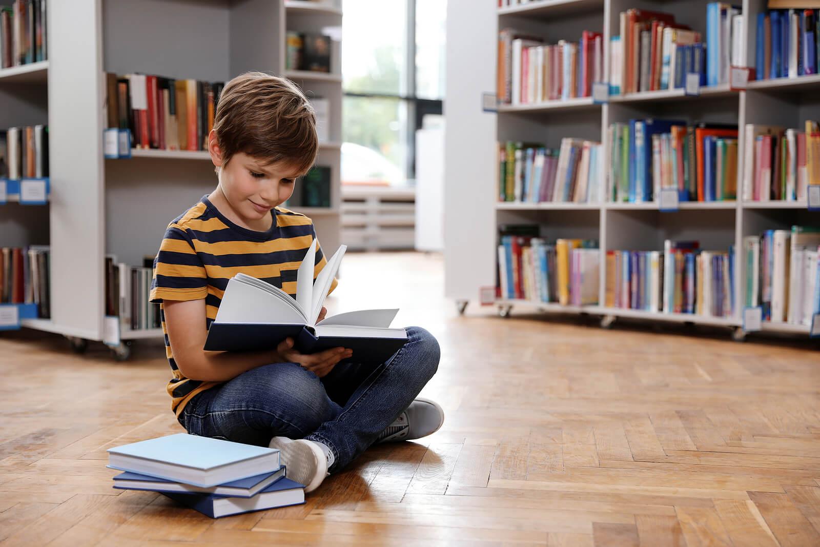 Niño leyendo un libro sentado en el suelo de la biblioteca.