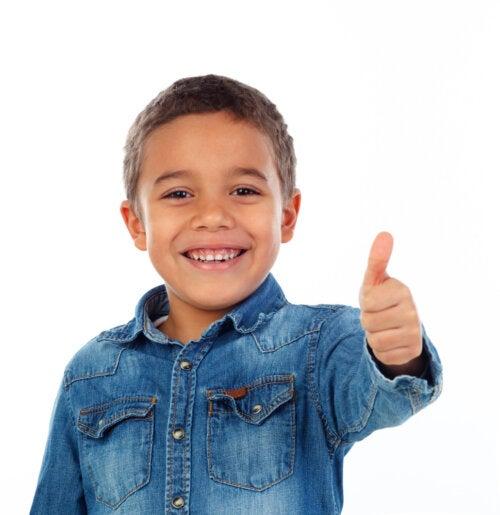Niño con el pulgar arriba, ejemplo de positividad gracias a su amor propio.