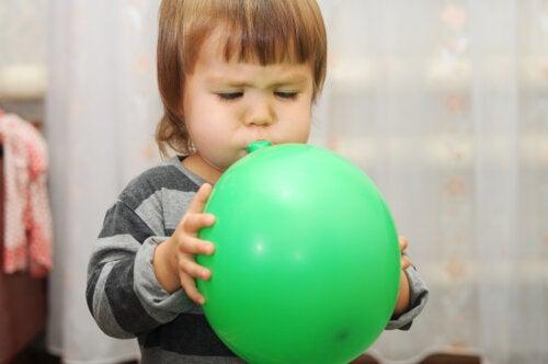 Niña soplando un globo para estimular el lenguaje.