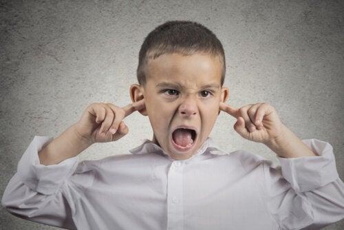 Niño con mal genio tapándose los oídos y gritando.