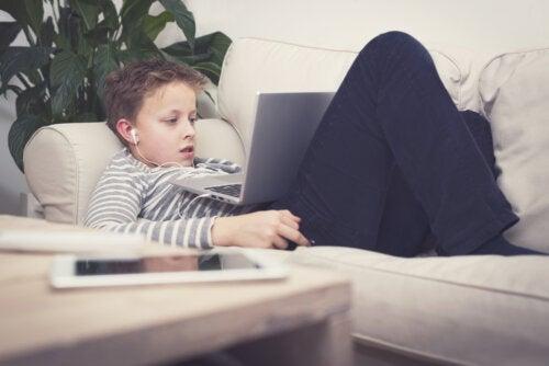 Niño consentido viendo series en el ordenador tumbado en el sofá.