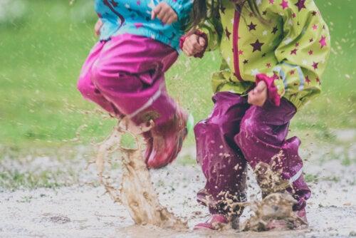 Niños jugando en el barro y manchándose.