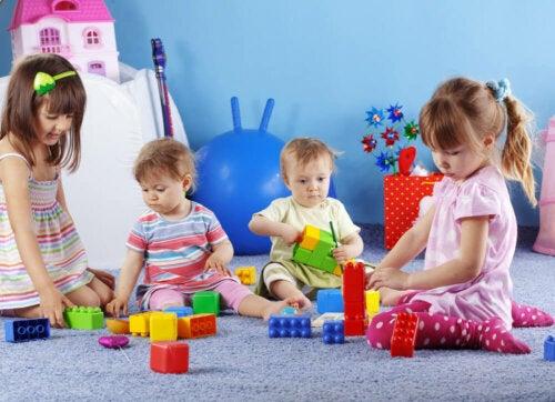 Bebés jugando con bloques para trabajar la motricidad.