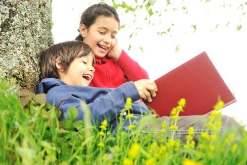 Niños leyendo un libro al aire libre.